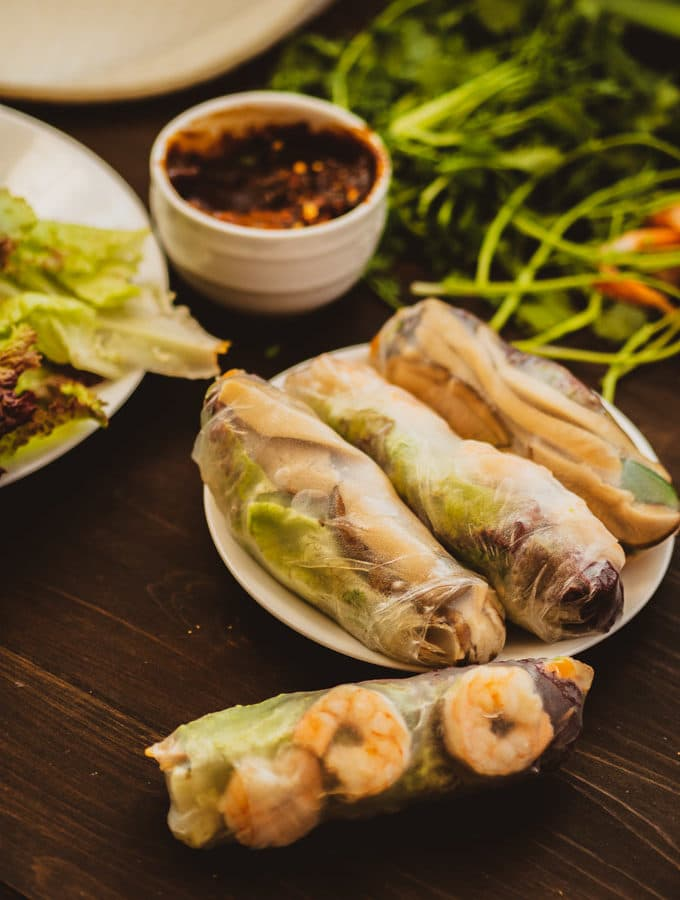 Spring rolls and dipping sauce with herbs in background