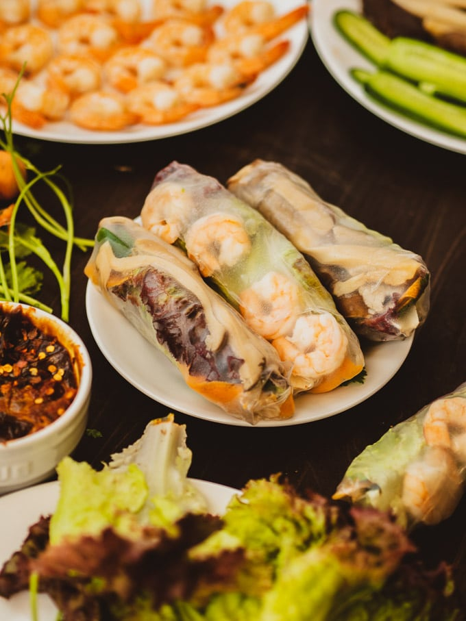 Plate of rolled spring rolls with shrimp in background and lettuce in foreground