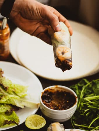 Vietnamese spring rolls dipped into peanut butter sauce