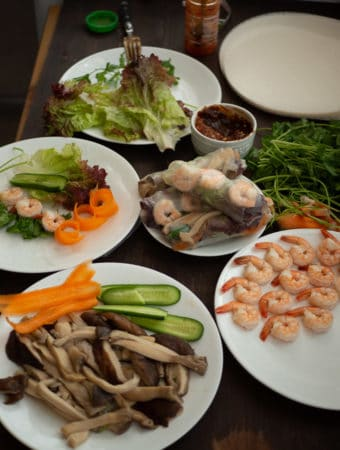 Ingredients for spring roll side by side on table including tofu, shrimp, dipping sauce, herbs