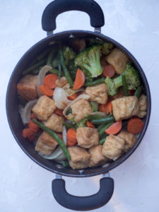 Cooked tofu and vegetables in curry sauce for Thai Green Curry with Tofu and Vegetable on a white background