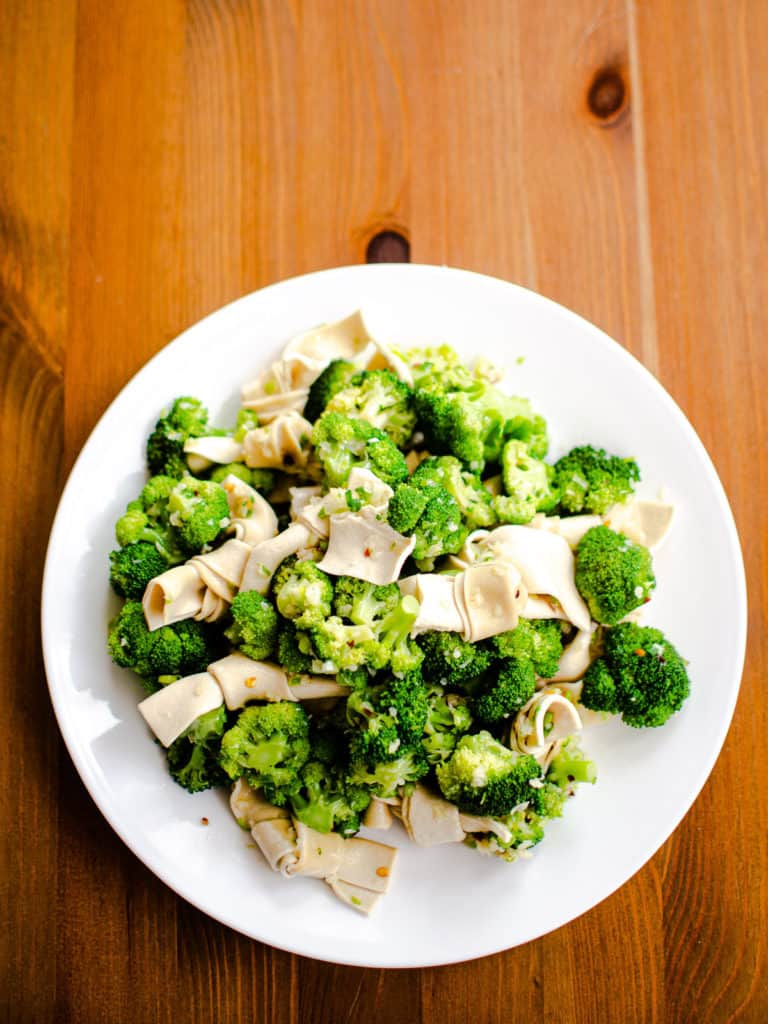 Tofu and broccoli salad dressed with spicy garlic-green onion sauce on a wood table