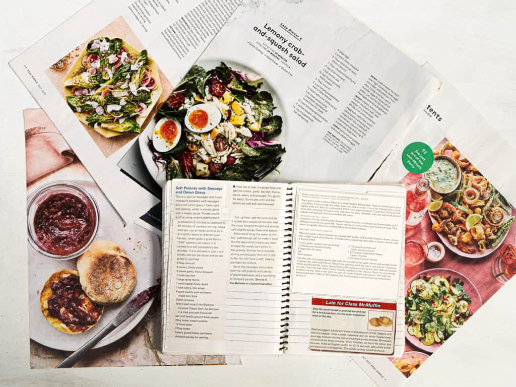 Anna's recipe swipe file stacked on top of magazine pages and recipes