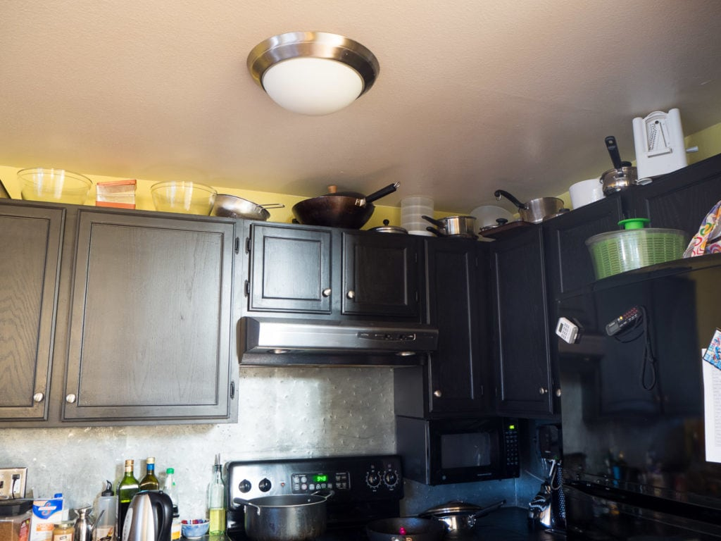 View of a kitchen with pots and pans on top of cabinets