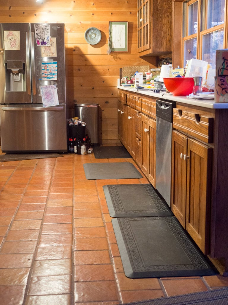 kitchen with floor mats next to fridge and counter