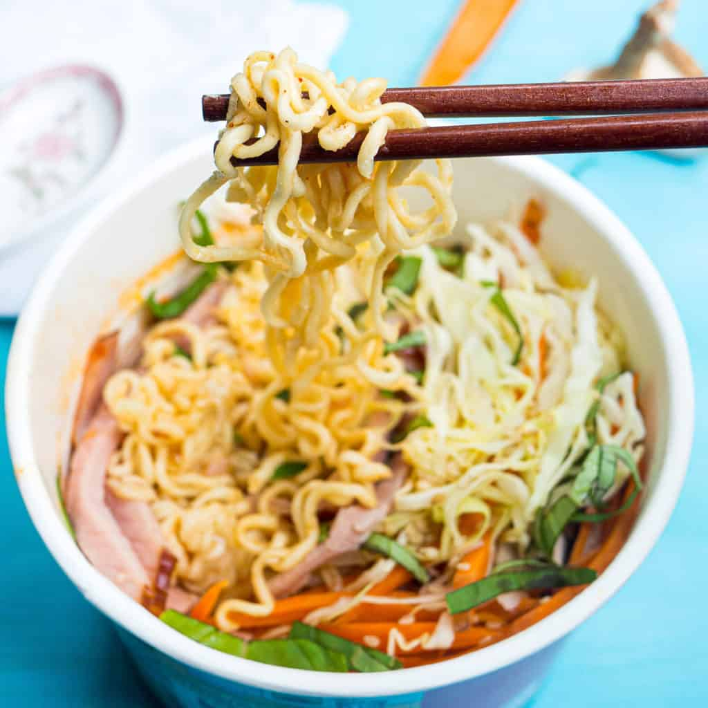 A pair of chopsticks picking up noodles with ham, cabbage, and basil nearby