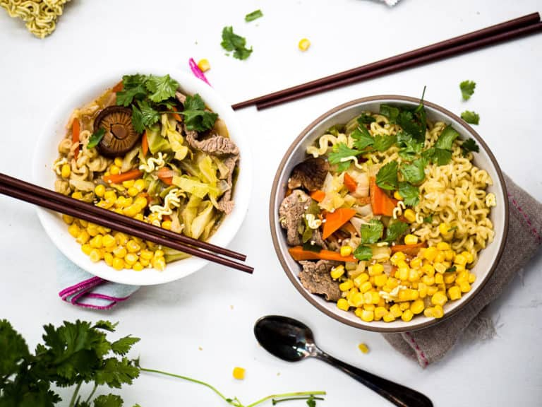 Two bowls of noodle soup with chopsticks, spoons, and cilantro on a white background