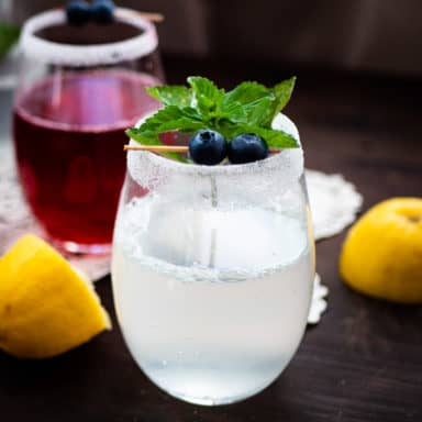 A glass of yellow lemonade and pink lemonade with mint and blueberry garnishes plus lemon wedges