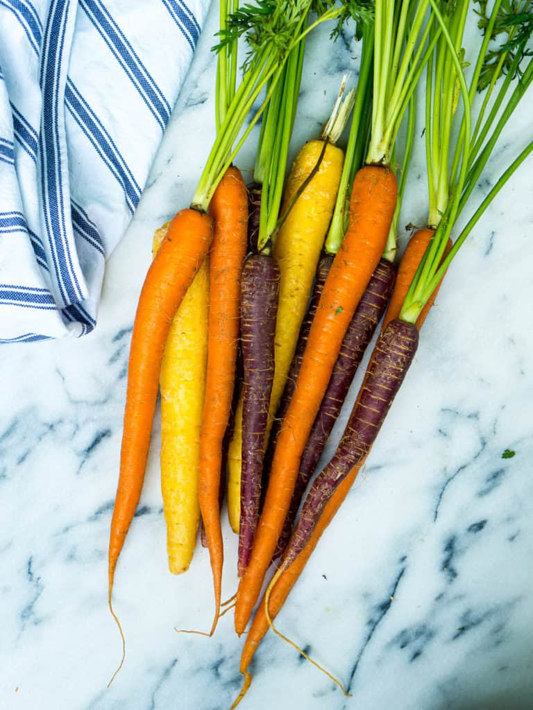 Orange, yellow, and purple carrots with leaves on a marble background