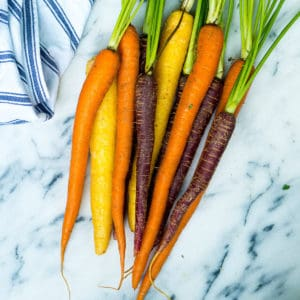 Orange, yellow, and purple carrots with leaves on a marble background next to a blue dish towel