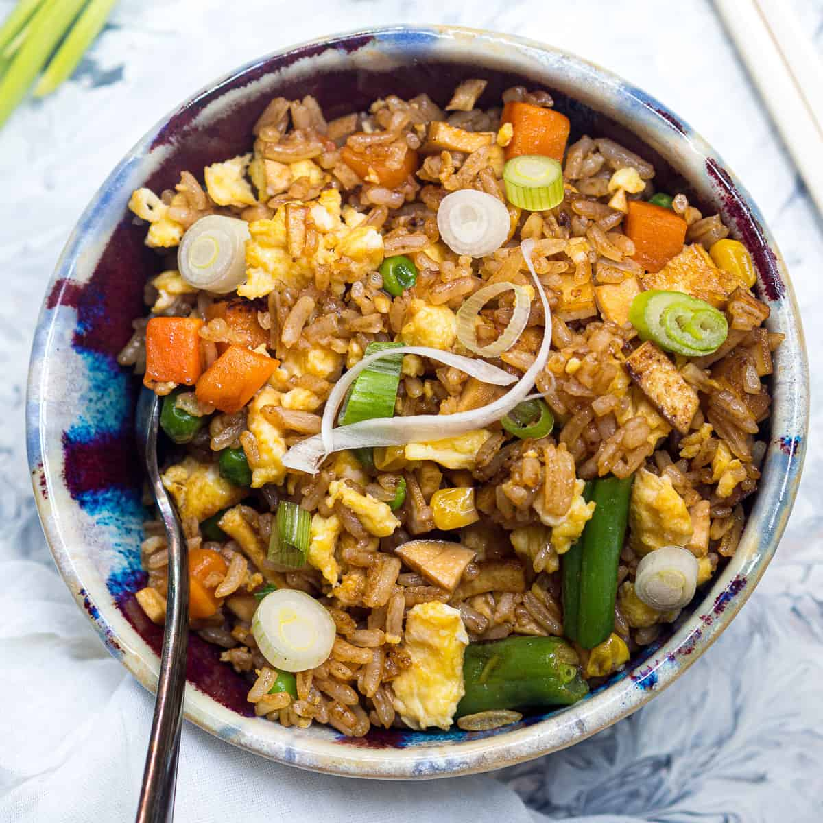 A bowl of fried rice with sliced green onions on top and a spoon in the bowl