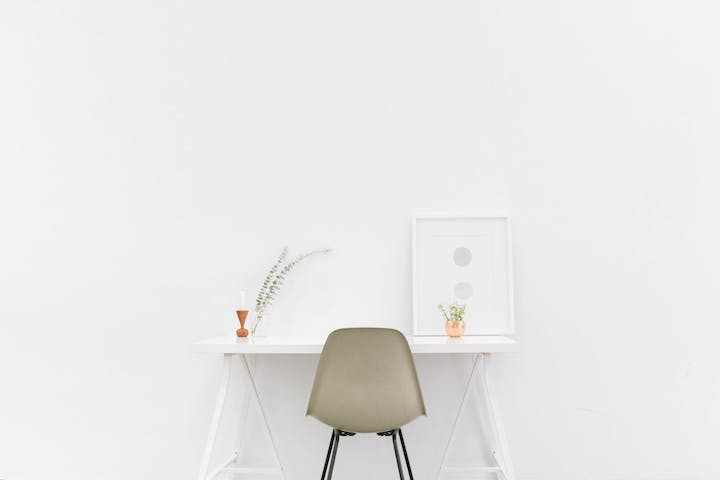 White chair pulled up to a white table next to a white wall representing minimalisming